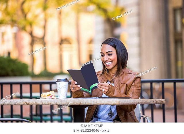 Indian woman reading booklet at outdoor cafe