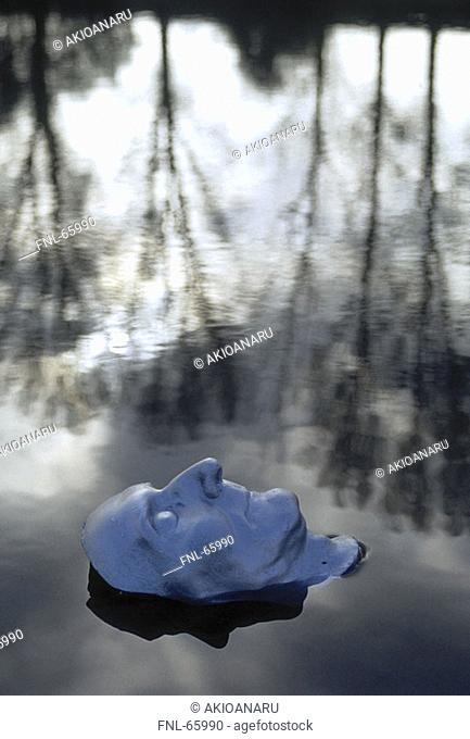 Close-up of head of mannequin floating in water