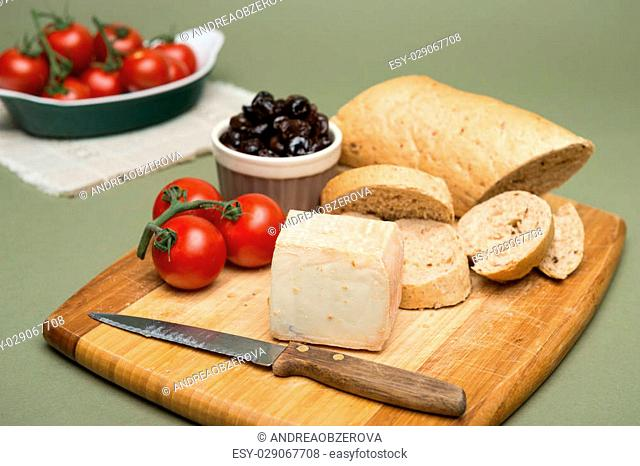 Bread and cheese/Delicious organic cream milk cheese, olives and home-made bread and ripe tomatoes on wooden board