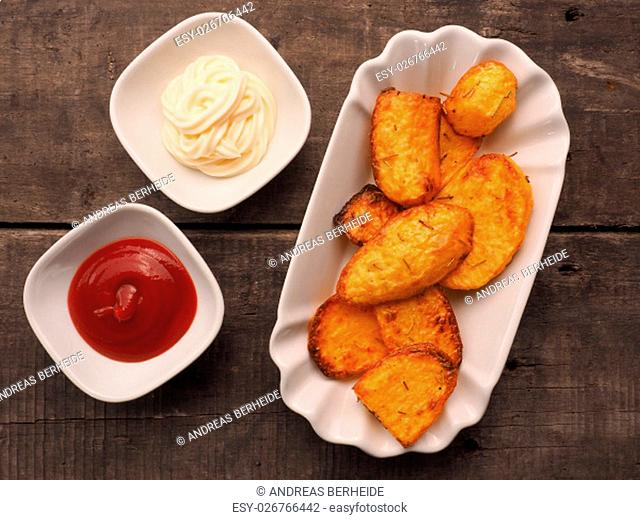 Rosemary potatoes with ketchup and mayonnaise on a wooden table