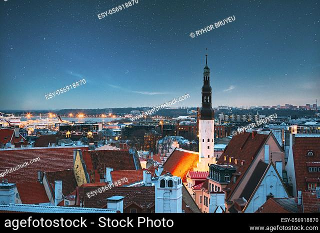 Tallinn, Estonia. Night Starry Sky Above Traditional Old Architecture Skyline In Old Town. Church Of Holy Ghost Or Holy Spirit In Winter Evening