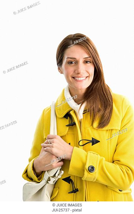 Smiling woman in yellow coat holding purse
