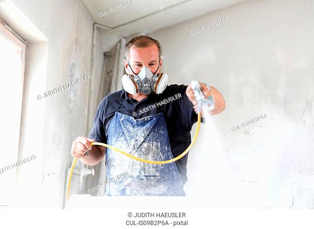 Man wearing protective mask spray painting timber