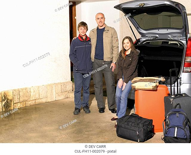 Father standing by car with son 11-13 and daughter 12-14