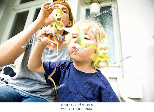 Toddler with mother on balcony blowing streamer