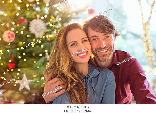 Portrait smiling couple hugging in front of Christmas tree