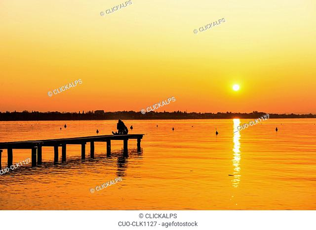 Loving couple kissing at sunset, Garda Lake, Veneto, Italy