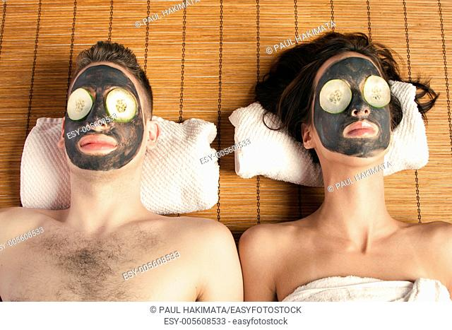 Couples holiday retreat at spa getting facial mask with cucumber skincare relaxing beauty treatment on bamboo