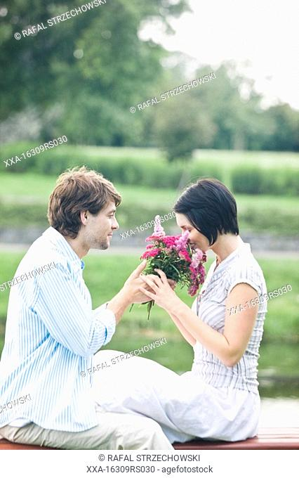 man giving flower to a woman in park