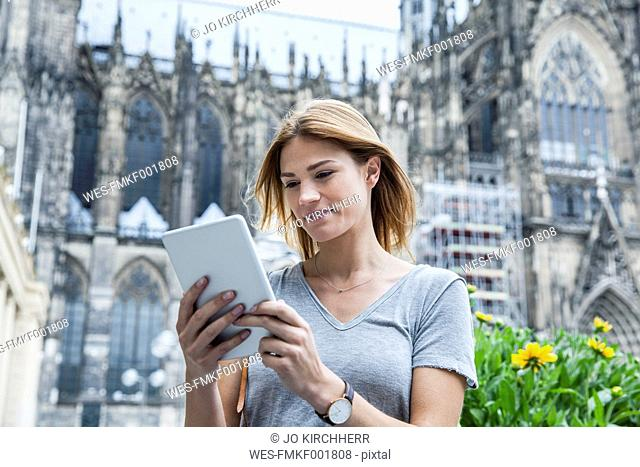 Germany, Cologne, portrait of young woman with mini tablet in front of Cologne Cathedral