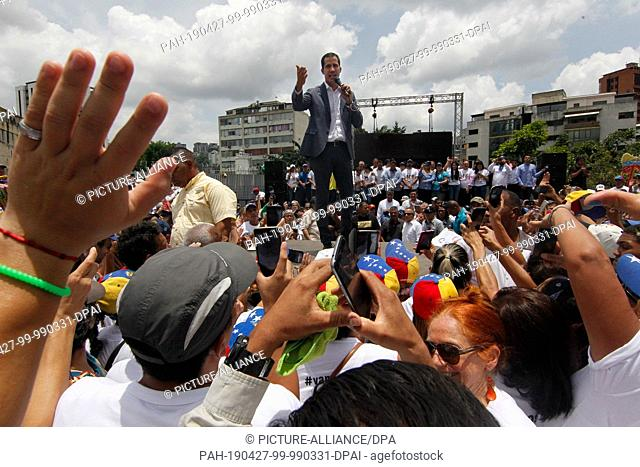 27 April 2019, Venezuela, Caracas: At a public rally in Caracas, Venezuelan opposition leader and self-proclaimed president Juan Guaido is giving a speech to...