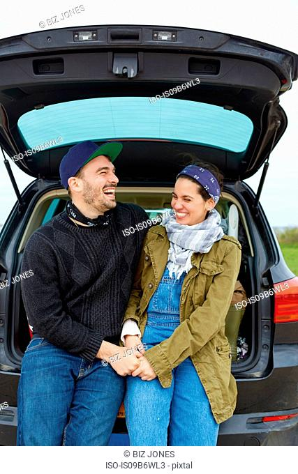 Young couple sitting in open boot of car, holding hands, laughing