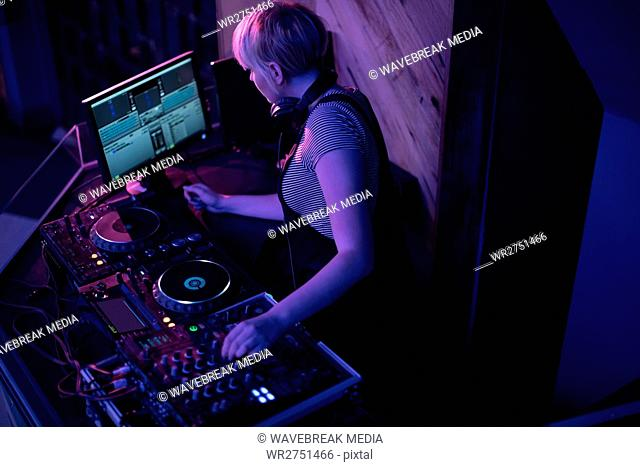 Female dj mixing music in bar