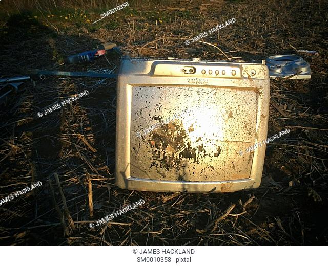 A television set sprayed with silver paint in a field amongst other unwanted items. Oakville, Ontario, Canada