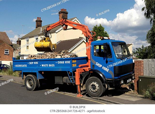 Grapple truck loading aggregate with a excavating arm, Ipswich, UK