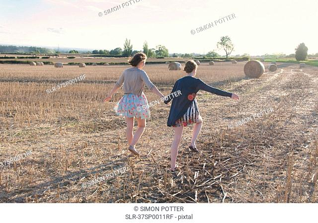 Girls running in hay field