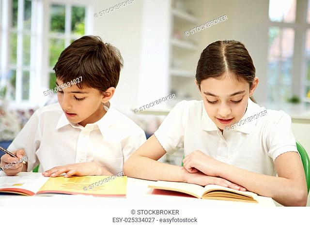 Children Wearing School Uniform Doing Homework In Kitchen