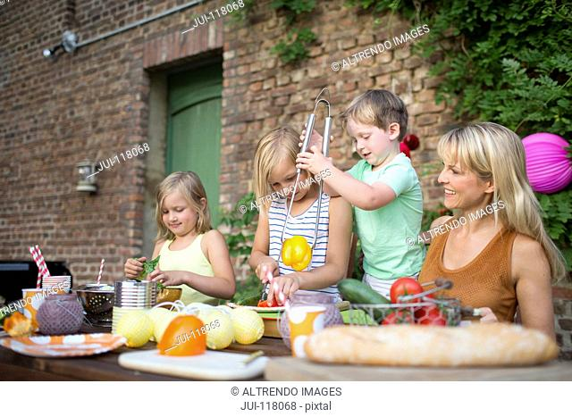 Mother With Children Eating Meal Outdoors At Home In Garden