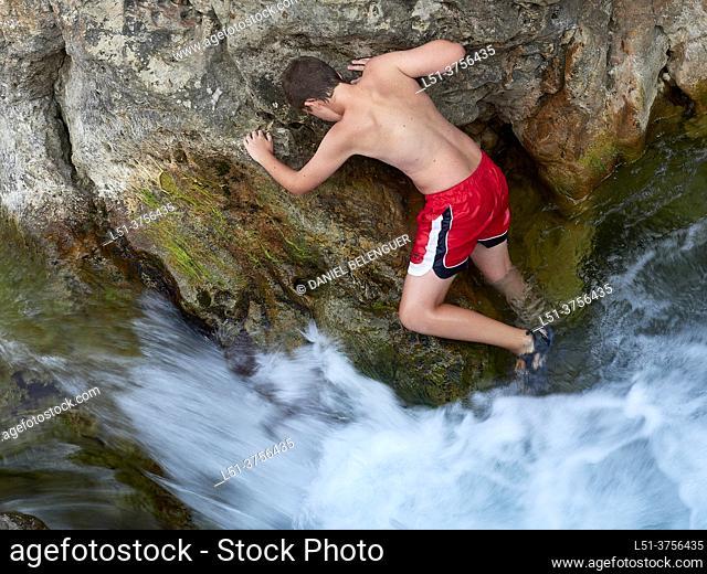 Boy climbing and walking through the Villahermosa river, Ludiente, Castellón, Spain