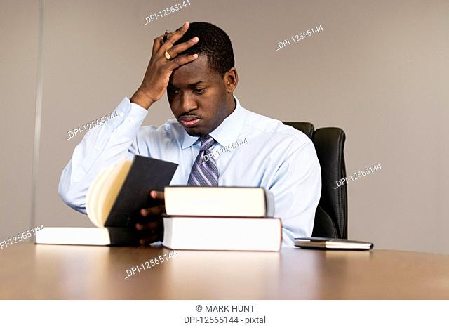 View of a tired young business man reading in an office