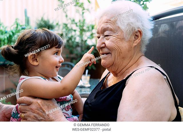 Grandmother and baby girl playing together on the terrace