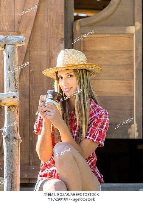 Countrygirl with cup of coffee in hand slight smile in wild west environment. Croatia