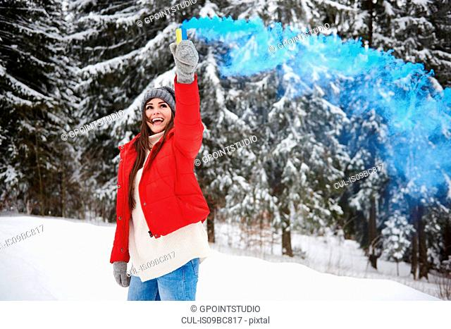 Young woman with smoke flare in snow