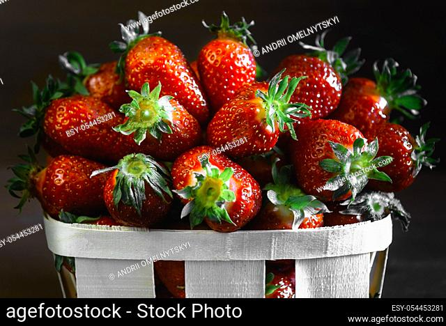 ripe juicy strawberries on a wooden table in a basket