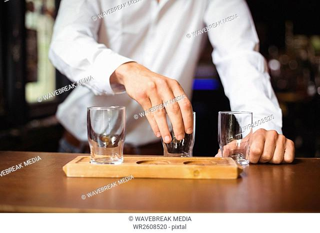 Bartender arranging beer glass on tray at bar counter