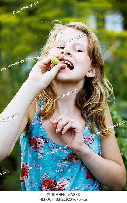 Girl eating green peas