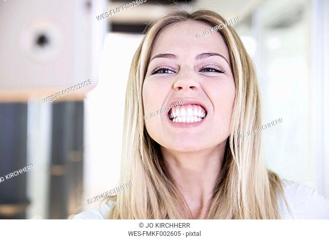 Blond woman at the dentist's taking selfie of bleached teeth