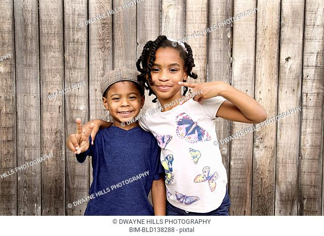 African American brother and sister hugging near wooden fence