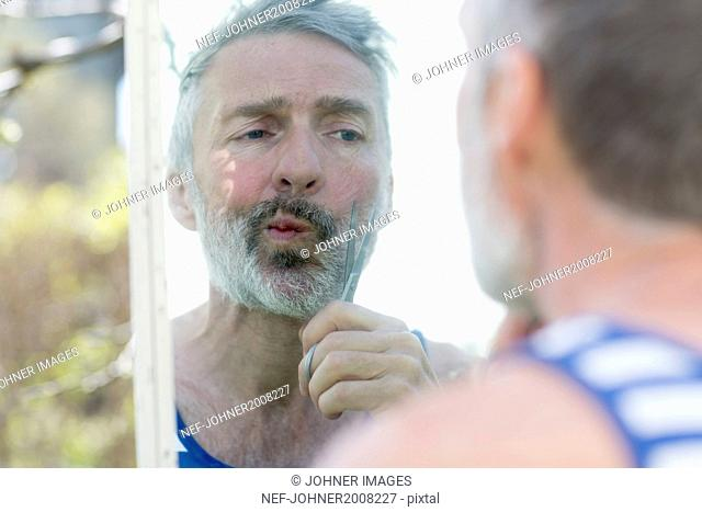 Man cutting beard in garden