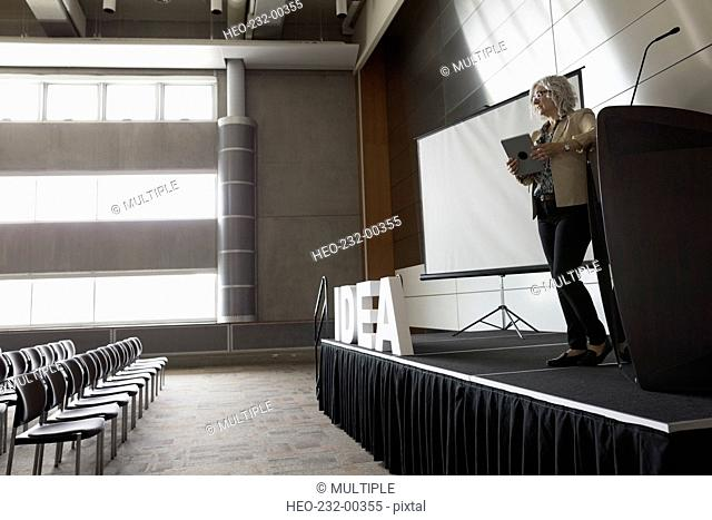 Woman with digital tablet on stage empty auditorium