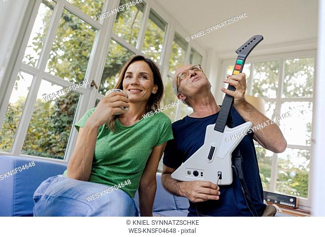 Mature couple sitting on couch at home with man playing toy electric guitar
