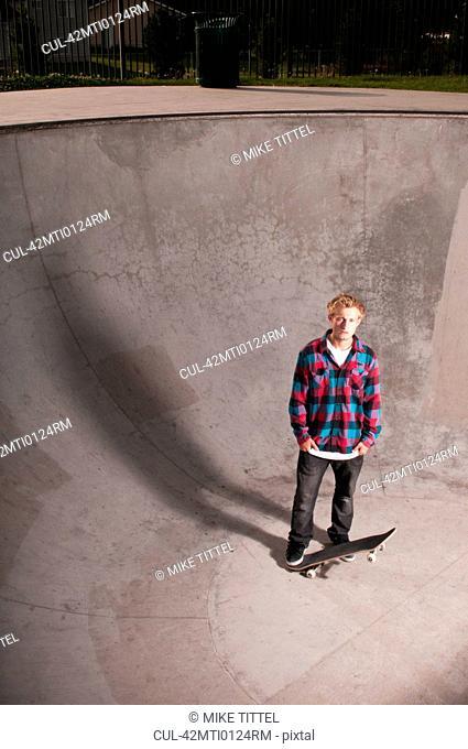 Skater standing with board in skatepark