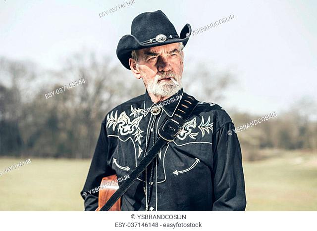Thoughtful senior Country and Western musician wearing a stylish black outfit standing holding his guitar outdoors with a serious expression