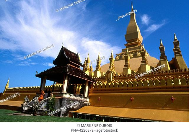 Two buddhist monks ascend the stairs of the golden Pha That Luang temple in Vientiane, Laos