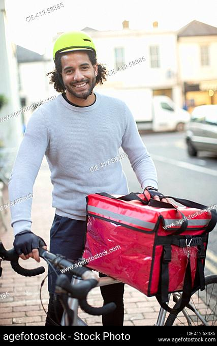 Portrait happy young male bike messenger in helmet delivering food