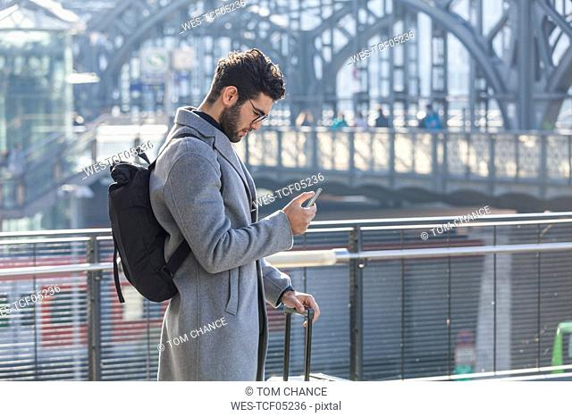 Businessman with baggage looking at cell phone at train station