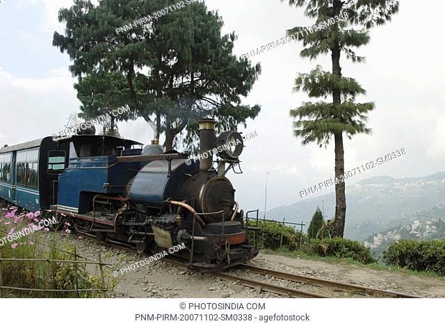 Steam train on railroad tracks, Darjeeling Himalayan Railway, Darjeeling, West Bengal, India