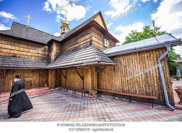 Priest in front of wooden Church of the Assumption of the Blessed Virgin in Chortkiv city in Ternopil Oblast of western Ukraine