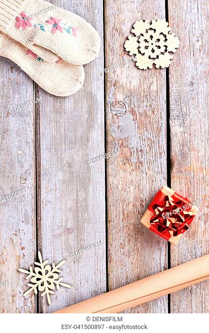New Year and Christmas wooden background. Cut out wooden snowflakes, handmade gift box, craft paper, knitted mittens on old wooden background, copy space