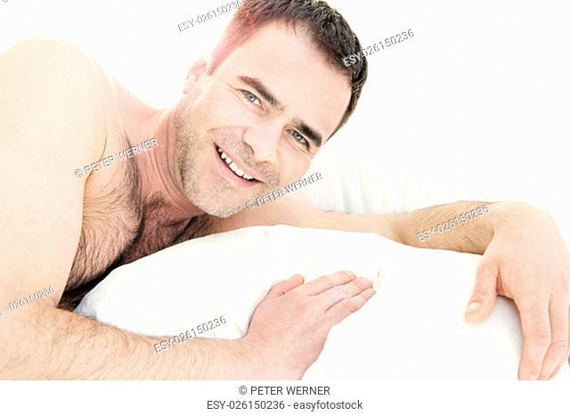 shirtless man in bed and smiling at camera