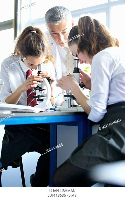 Teacher helping high school students using microscopes in biology class