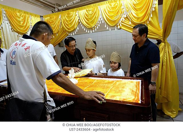 The eldest son asks some money from the late dad. Sarawakian chinese funeral ceremony. Malaysia
