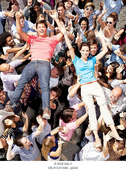 Portrait of man and woman crowd surfing