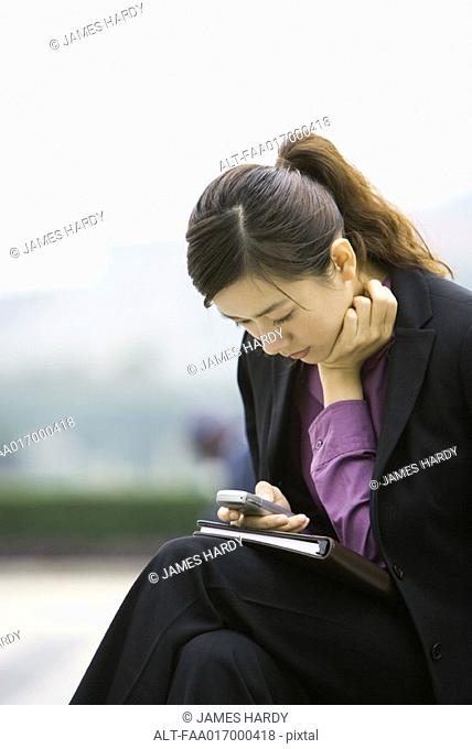 Businesswoman using messaging phone, leaning forward