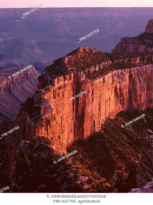Sunset reddens vertical cliffs of Wotans Throne, from Cape Royal, North Rim, Grand Canyon National Park, Arizona, USA