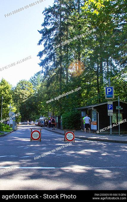 """06 August 2020, Saxony, Lohmen: There are two traffic signs in front of the full parking lot at the Bastei near Lohmen. On the left one is """"""""Closed for cars"""